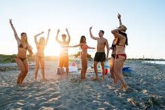 Grupo de amigos que fazem o partido na praia no tempo do por do sol foto de stock