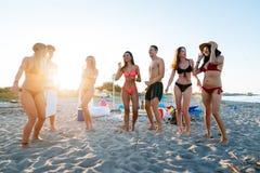Grupo de amigos que fazem o partido na praia no tempo do por do sol fotografia de stock royalty free