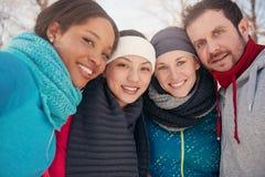 Grupo de amigos que gozan en la nieve en invierno Fotografía de archivo