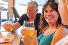 Grupo de amigos que gozan de los vidrios de cerveza micro del brebaje en la barra fotos de archivo libres de regalías