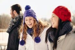 Grupo de amigos que gozan que cuelga hacia fuera en invierno Imagen de archivo