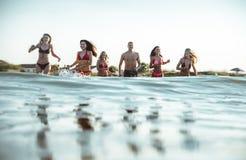 Grupo de amigos que hacen el partido en la playa en el tiempo de la puesta del sol Imagen de archivo