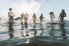 Grupo de amigos que hacen el partido en la playa en el tiempo de la puesta del sol Fotos de archivo libres de regalías