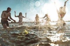Grupo de amigos que hacen el partido en la playa en el tiempo de la puesta del sol Imagen de archivo libre de regalías