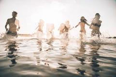 Grupo de amigos que hacen el partido en la playa en el tiempo de la puesta del sol Foto de archivo libre de regalías