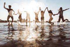 Grupo de amigos que hacen el partido en la playa en el tiempo de la puesta del sol Fotografía de archivo