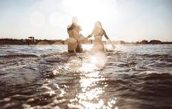 Grupo de amigos que hacen el partido en la playa en el tiempo de la puesta del sol Foto de archivo