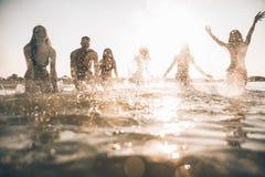 Grupo de amigos que hacen el partido en la playa en el tiempo de la puesta del sol Fotografía de archivo libre de regalías