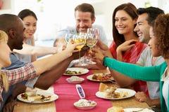Grupo de amigos que hacen la tostada alrededor de la tabla en el partido de cena Imágenes de archivo libres de regalías