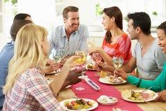 Grupo de amigos que hacen la tostada alrededor de la tabla en el partido de cena Fotografía de archivo