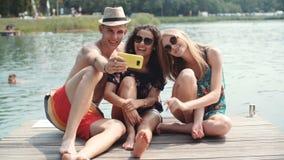 Grupo de amigos que hacen selfies por el lago metrajes