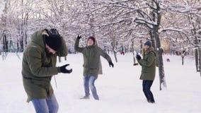 Grupo de amigos que jogam bolas de neve e que têm o divertimento no parque nevado, movimento lento vídeos de arquivo