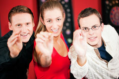Grupo de amigos que jogam dardos Imagens de Stock Royalty Free