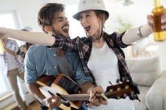 Grupo de amigos que jogam a guitarra e que partying em casa imagem de stock