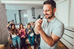 Grupo de amigos que jogam o karaoke em casa foto de stock