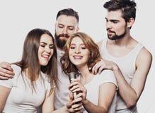 Grupo de amigos que jogam o karaoke sobre o fundo branco conceito sobre a amizade e os povos imagens de stock royalty free