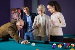 Grupo de amigos que juegan billares y que sonríen en sitio de billar Imágenes de archivo libres de regalías
