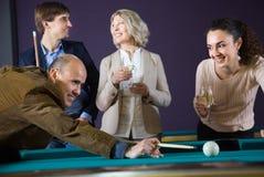 Grupo de amigos que juegan billares y que sonríen en sitio de billar Fotos de archivo libres de regalías