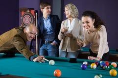 Grupo de amigos que juegan billares y que sonríen en sitio de billar Fotos de archivo
