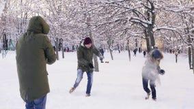 Grupo de amigos que juegan bolas de nieve y que se divierten en parque nevoso, cámara lenta almacen de video