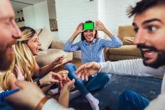 Grupo de amigos que juegan charadas en casa fotografía de archivo