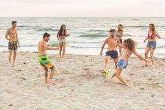 Grupo de amigos que juegan con la bola en la playa Foto de archivo
