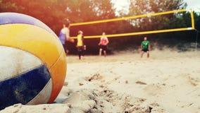 Grupo de amigos que juegan el primer del voleibol de playa de la bola en arena almacen de video