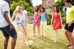 Grupo de amigos que juegan a fútbol en jardín Fotos de archivo libres de regalías