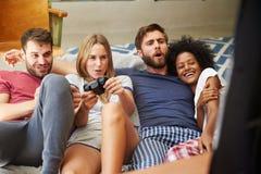 Grupo de amigos que llevan los pijamas que juegan al videojuego junto Foto de archivo