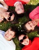 Grupo de amigos que mienten en la hierba que mira para arriba Imágenes de archivo libres de regalías