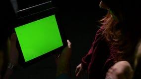 Grupo de amigos que miran el contenido en línea en la PC verde de la tableta de la pantalla y que hablan de él metrajes