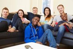 Grupo de amigos que miran la televisión en casa junto Imágenes de archivo libres de regalías