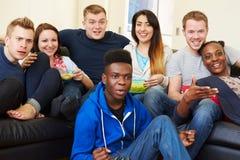 Grupo de amigos que miran la televisión en casa junto Foto de archivo