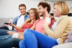 Grupo de amigos que miran la televisión junto en casa Foto de archivo