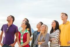 Grupo de amigos que miran para arriba en la playa Fotos de archivo libres de regalías