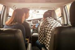 Grupo de amigos que miran un mapa en el teléfono celular en concepto del viaje por carretera del coche imagen de archivo