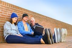 Grupo de amigos que miran un ordenador portátil después de universidad Foto de archivo