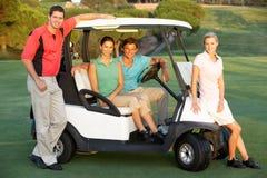 Grupo de amigos que montan en cochecillo del golf Foto de archivo libre de regalías