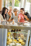 Grupo de amigos que olham o café dos bolos Fotografia de Stock