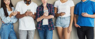 Grupo de amigos que olham telefones espertos, panorama imagens de stock royalty free