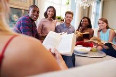 Grupo de amigos que participam no clube de leitura em casa fotografia de stock
