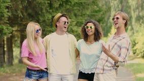 Grupo de amigos que penduram para fora no parque no dia ensolarado, rindo de gracejos, tendo o divertimento filme