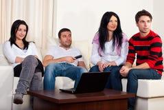 Grupo de amigos que prestam atenção à tevê Imagem de Stock