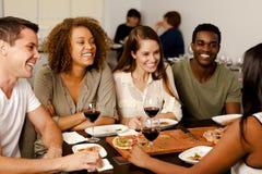 Grupo de amigos que ríen en un restaurante Imagen de archivo libre de regalías