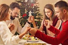 Grupo de amigos que ruegan sobre la tabla de la Navidad imagenes de archivo