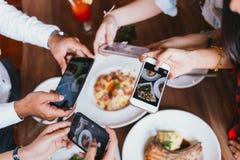 Grupo de amigos que saem e que tomam uma foto do alimento italiano junto com o telefone celular imagem de stock