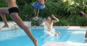 Grupo de amigos que saltan en piscina almacen de video