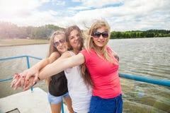 Grupo de amigos que se divierten al aire libre en un lago Foto de archivo libre de regalías