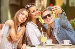 Grupo de amigos que se divierten con un teléfono elegante imágenes de archivo libres de regalías