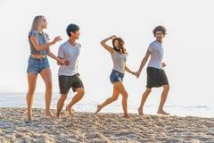 Grupo de amigos que se divierten que corre abajo de la playa en la puesta del sol foto de archivo libre de regalías